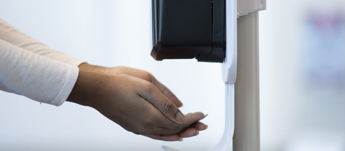 Medical Professional using a touchless sanitizer dispenser